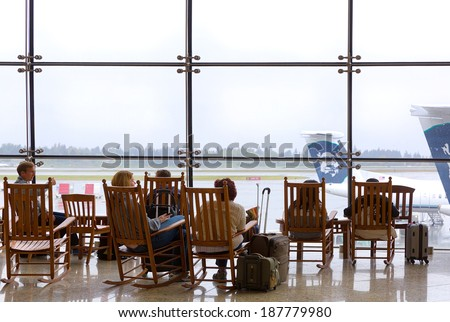 SEATTLE-APR 16, 2014: Travelers rest in wooden rocking chairs in the main terminal at SEATAC, the Seattle-Tacoma International Airport. The old fashioned chairs are much loved, say airport officials. - stock photo