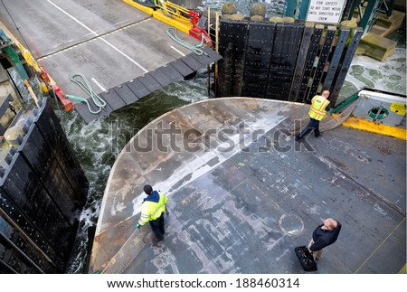 SEATTLE-APR 14, 2014: Washington State Ferry deckhands prepare a car ferry for landing in Seattle. WSF operates 22 ferries carrying more than 22 million passengers to 20 different ports of call.  - stock photo