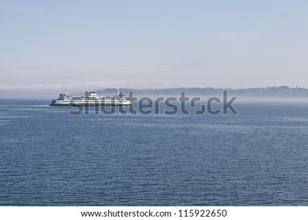 SEATTLE - AUGUST 14: A ferry aprroaches Seattle through the early morning mist across Puget Sound, August 14, 2012 in Seattle. Each ferry has a capacity of 2,500 passengers and 202 vehicles. - stock photo