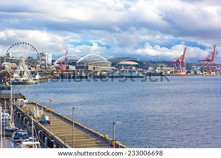 Seattle Great Wheel and port cranes under blue cloudy sky in Seattle downtown. Late afternoon sun touched piers along Alaskan Way in Seattle downtown. - stock photo