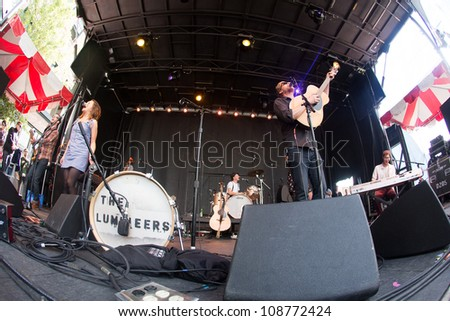 SEATTLE - JULY 25:  Wesley Shultz of the popular folk band the Lumineers performs with Jeremiah Friates and Neyla Pekarek on the main stage at the Capitol Hill Block Party in Seattle on July 22, 2012 - stock photo