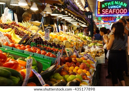 SEATTLE - JUN 3, 2016 - Young women buy fresh fruit at the Pike Place Market