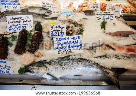 SEATTLE - MAY 10: A fresh wild Alaskan king salmon is displayed at City Fish Co. at Pike Place Market in Seattle on May 10, 2014. City Fish Co. opened in 1917. - stock photo