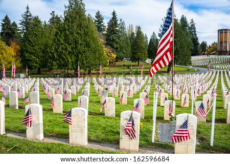 SEATTLE - NOV 11: Headstones, including Medal of Honor Recipient, with Flags in Arlington of the West Veterans Memorial Cemetery at Evergreen Washelli Memorial Park in Seattle WA on Nov 11, 2013. - stock photo