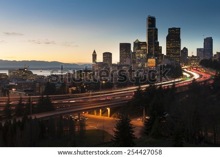 Seattle Skyline. A lovely Seattle sunset during rush hour where freeways are congested with traffic. Elliott Bay and the Olympic Mountains can be seen in the background. - stock photo