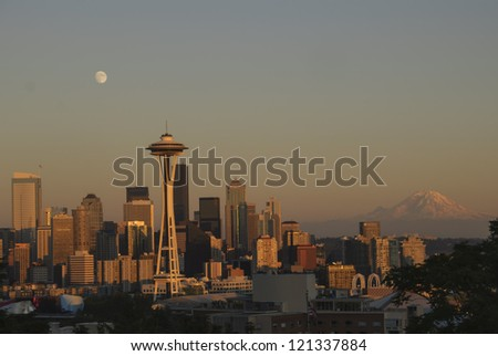 Seattle Skyline with full moon and Mt. Rainier at sunset. - stock photo