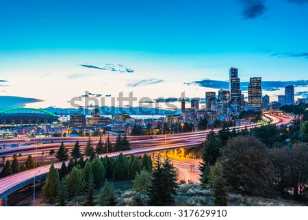 Seattle skylines and Interstate freeways converge with Elliott Bay and the waterfront background of in sunset time, Seattle, Washington State, USA. - stock photo