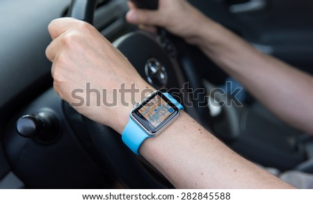 SEATTLE, USA - May 30, 2015: Man Using Maps App on Apple Watch While Driving Toyota Prius - stock photo