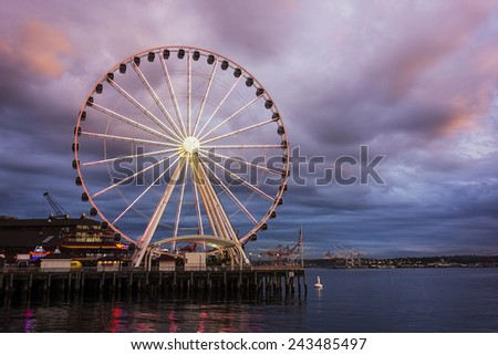 SEATTLE, USA - OCTOBER 14, 2014:  The Big Wheel stands against a cloudy sunset at the end of a pier on Elliott Bay at night in Seattle, Washington on October 14, 2014.