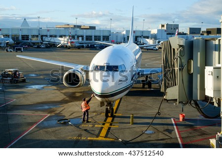 Seattle, WA, USA June 10, 2016: Passenger jet airplane at terminal with jetway. Boeing 737. Tarmac worker connects jet to ground control