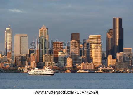 SEATTLE, WASHINGTON - AUGUST 3: A scenic cruise ship crosses in front of the Seattle skyline as viewed from Alki Beach Park on August 3, 2013 in Seattle, Washington - stock photo