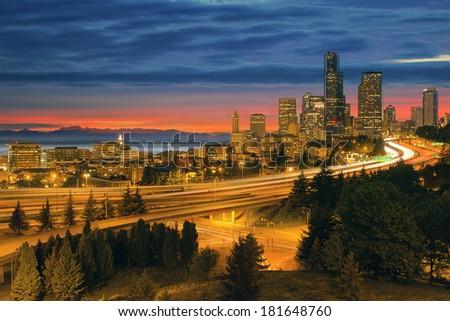 Seattle Washington City Skyline with Freeway Light Trails After Sunset - stock photo