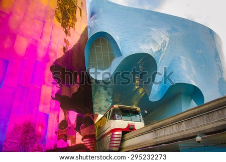 SEATTLE, WASHINGTON - DECEMBER 14, 2014: The Monorail enters the 1962 World's Fair site through the ultra-modern EMP Museum with the Space Needle reflected on the Museum's walls.