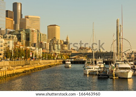 SEATTLE, WASHINGTON - OCTOBER 6: Seattle waterfront with Seattle downtown view on October 6, 2012 in Seattle. Many people come to Alaskan way to enjoy the beautiful sunset.  - stock photo