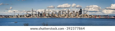 Seattle, Washington Panorama.  A lovely spring day along the Seattle, Washington waterfront. This panoramic view features puffy clouds, ferryboats, the Space Needle, and modern office buildings.  - stock photo