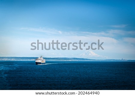 SEATTLE, WASHINGTON, USA - JUNE 21:  A commercial cruise ship leaves port in Seattle on June 21, 2014, with Mount Rainier and Seattle skyline in the background. - stock photo