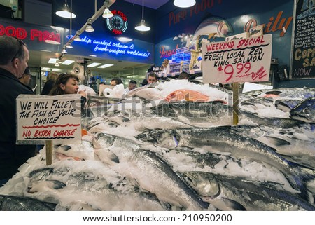 SEATTLE, WASHINGTON, USA - JUNE 28:  Tourists browse in a fish market at Pikes Place in Seattle, WA on June 28, 2014.  Pike Market Place is Seattle's original farmer's market. - stock photo
