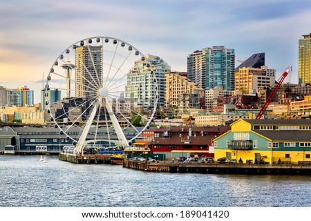 Seattle waterfront and skyline, with the Space Needle showing through the spokes of the Great Wheel ferris wheel in the foreground. Colorful image with late afternoon gold light. - stock photo