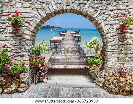 Seaview through the stone arch with flowers in Italy - stock photo