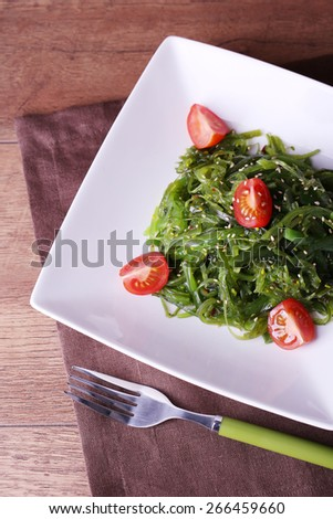 Seaweed salad with slices of cherry tomato in plate on napkin and wooden table background - stock photo