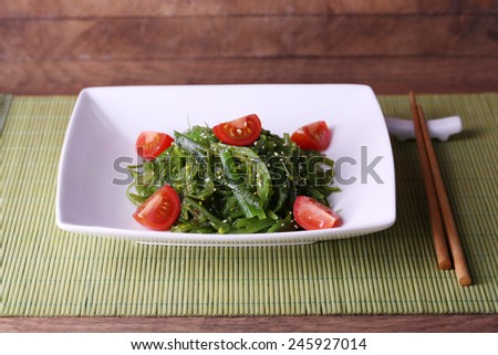 Seaweed salad with slices of cherry tomato on bamboo mat and wooden table background - stock photo