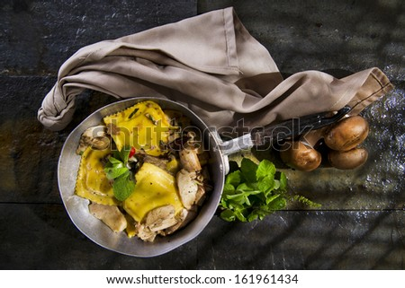 Second Dish With Ravioli With Mushroom Sauce Presented In a Frying Pan - stock photo