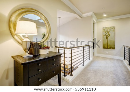 Second floor landing with black console table topped with a lamp placed under round gold mirror. Northwest, USA