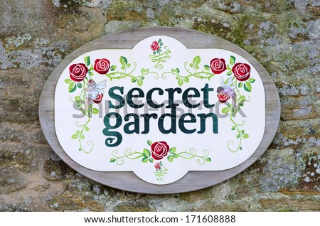 Secret garden sign on weathered stone wall - stock photo