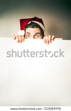 Secret santa advertising christmas products and gifts while hiding behind blank copyspace banner - stock photo