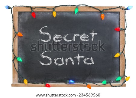Secret Santa written in white chalk on a black chalkboard surrounded with colored lights isolated on white - stock photo