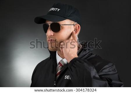 Secret Service Agent Listening To Earpiece Over Black Background - stock photo