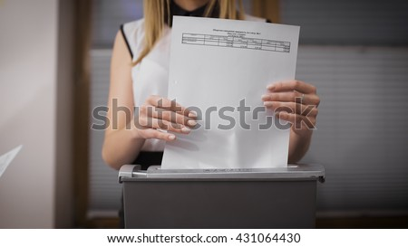 Secretary destroys documents using a special apparatus. Hiding confidential financial information. Close-up on the girl's hands - stock photo