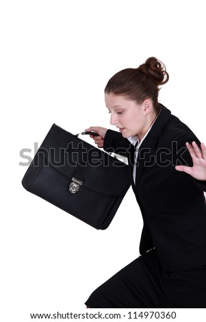 secretary holding briefcase trying to keep her balance - stock photo