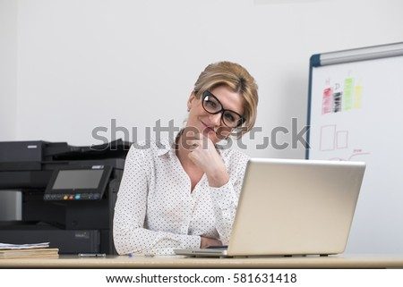 Secretary in the office. Portrait of a beautiful young woman in a white blouse and black skirt on office background
