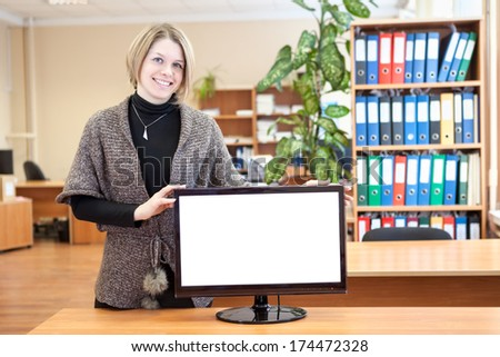 Secretary in the office standing next to a white screen monitor - stock photo