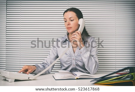 secretary on the phone at office. Businesswoman