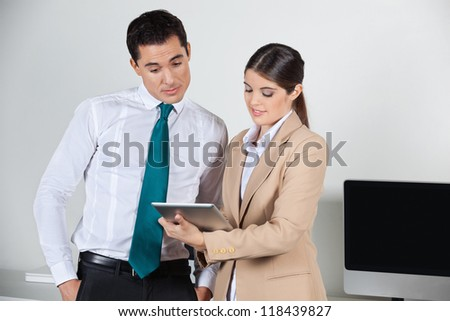Secretary planning dates for her boss with a tablet pc in the office