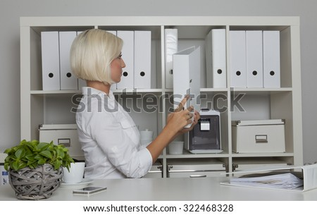 secretary puts back a folder from her desk into the cabinet