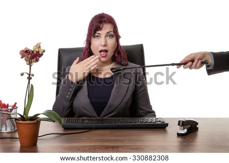 secretary sitting at desk with a man hand holding a riding whip up to her throat
