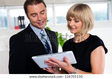 Secretary with tablet pc discussing the schedule with her boss. Business concept