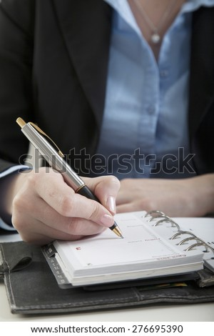 secretary writes down an entry into the calendar of her diary - stock photo