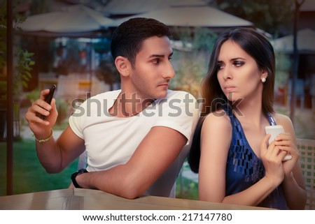Secretive Couple with Smart Phones in Their Hands - Young adult couple has privacy problems with modern technology  - stock photo