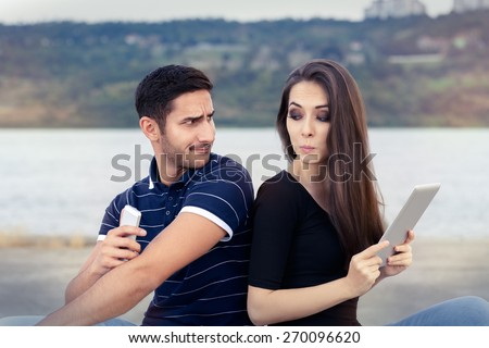 Secretive Couple with Tablet and Smartphone - Young adult couple has privacy problems with modern technology