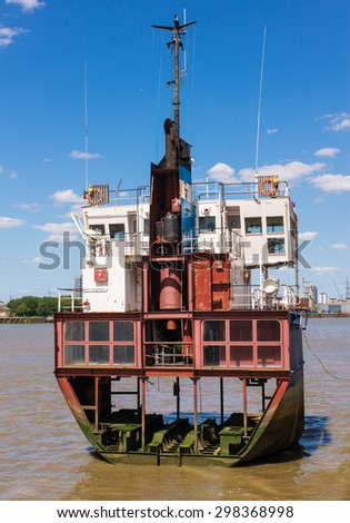 Section of an old boat cut in half laying on muddy water - stock photo