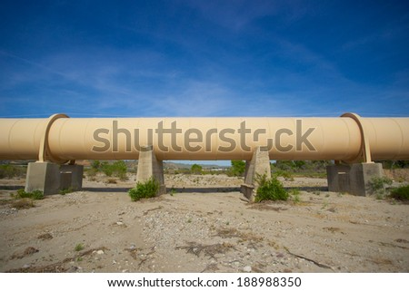 Section of massive metal pipeline cross the sand of the Mojave Desert. - stock photo