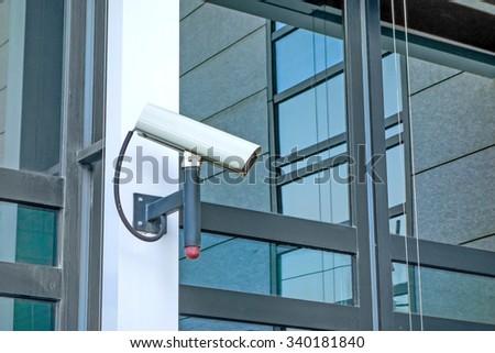 Security camera at modern building facade - stock photo