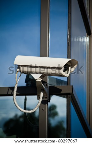 Security camera attached on business building with reflections - stock photo