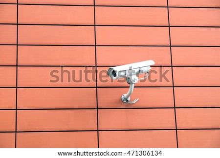 Security camera mounted on modern building orange wall horizontal view closeup