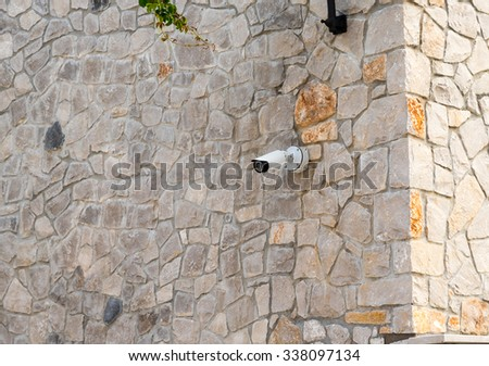 security camera on a stone wall - stock photo