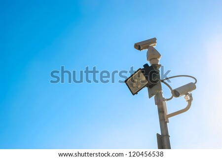security camera on blue sky background - stock photo